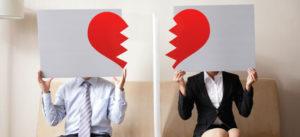 couple hiding their faces in a broken heart signs