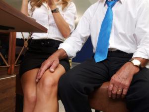 A man sexually harassing a woman by touching the legs